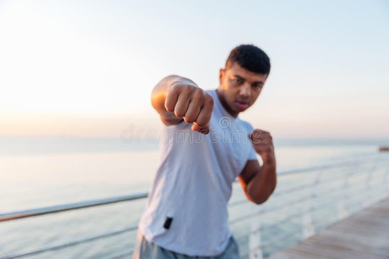 Idrotts- afrikansk manboxare som gör boxningutbildning på pir fotografering för bildbyråer