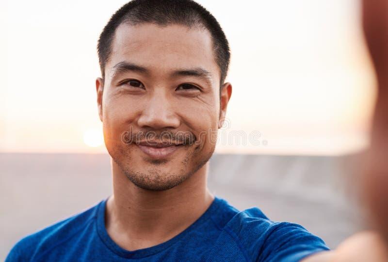 Idrotts- asiatisk man som ler medan ut för en morgonkörning arkivbilder