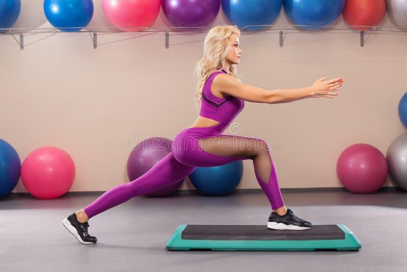 Idrotts- flicka som gör sträcka övning i konditionrummet Sportkvinna i sportsweargenomkörare royaltyfria bilder