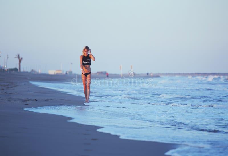 Idrotts- flicka som promenerar stranden en fantastisk solnedgång med havet på bakgrund royaltyfria foton