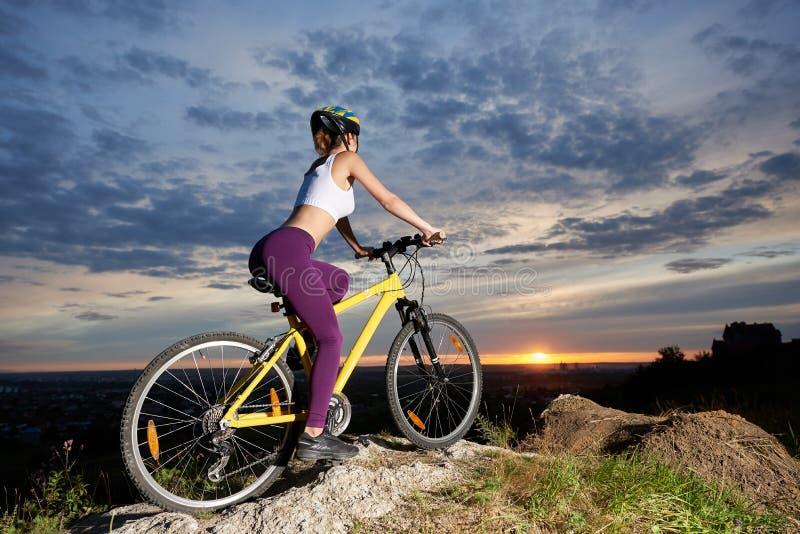 Idrotts- flicka som sitter på cykeln och tycker om stor sikt arkivbild