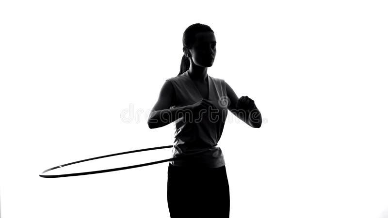 Idrotts- flicka som vrider hulabeslaget som övar för att förlora vikt, sportlivsstil royaltyfri fotografi