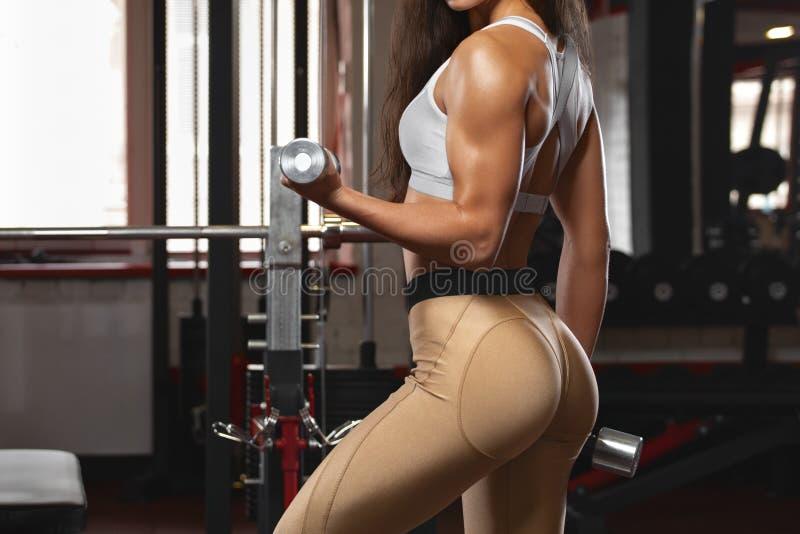 idrotts- flickagenomk?rare i idrottshall Konditionkvinna som g?r ?vningen f?r biceps H?rliga bakdelar i damasker arkivbilder