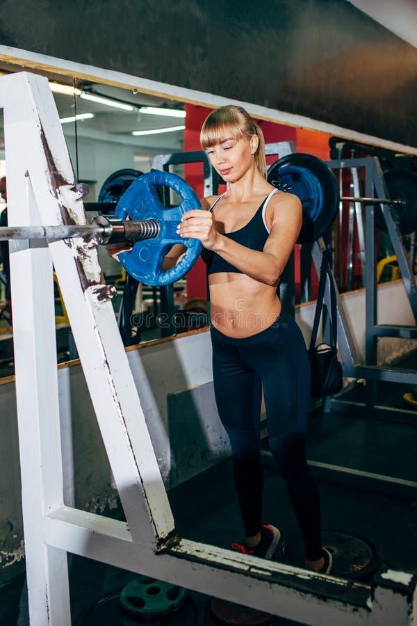 Idrotts- flickauppsättningvikt på skivstång i idrottshallen arkivfoto
