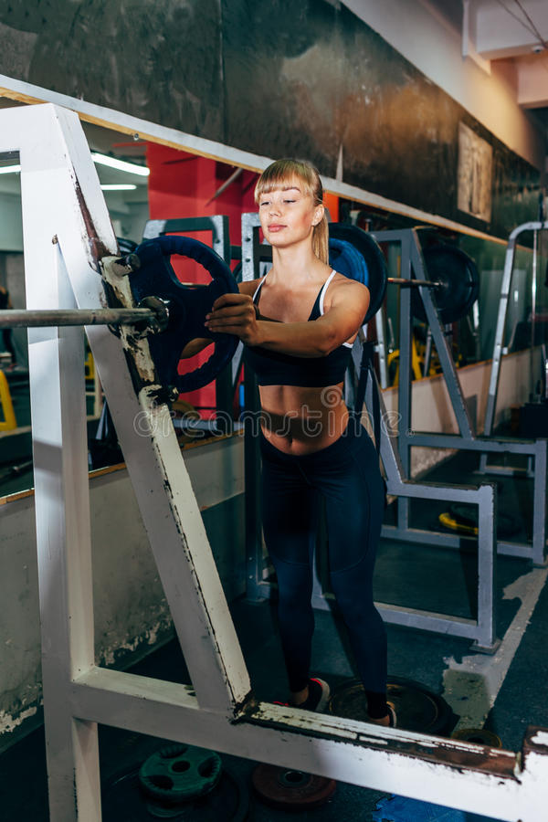 Idrotts- flickauppsättningvikt på skivstång i idrottshallen arkivfoton