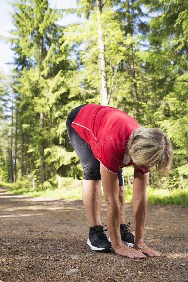 Idrotts- hög sträckning efter jogga övning arkivbild