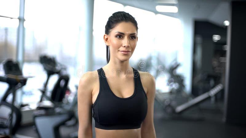 Idrotts- konditionkvinna i idrottshallen som ser kameran, aktiv livsstil, sportklubba royaltyfri bild