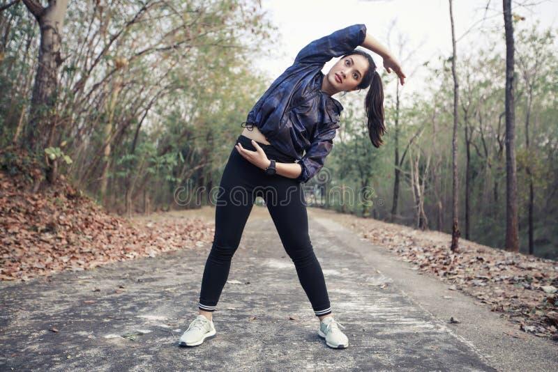 Idrotts- kvinna asia uppvärmning och ung exercisi för kvinnlig idrottsman nen arkivbilder