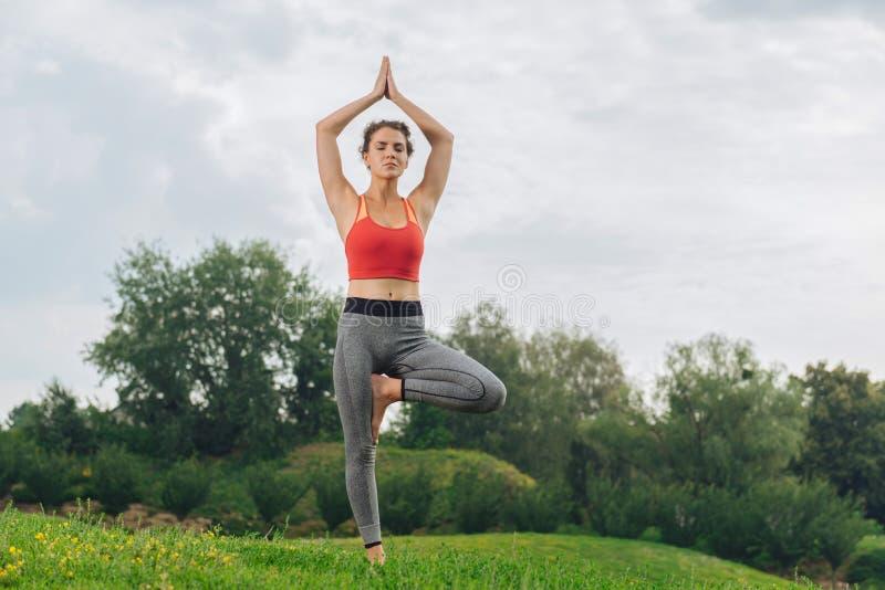 Idrotts- kvinna som bär bästa görande yoga för ljus röd sport royaltyfria foton