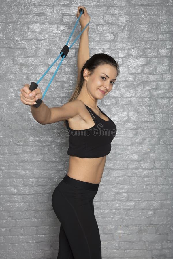 Idrotts- kvinna som gör övningar med gummi arkivfoto