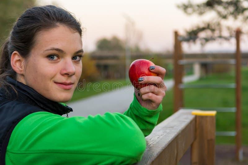 Idrotts- kvinna som har ett sunt fruktmellanmål under utomhus- övning arkivbilder