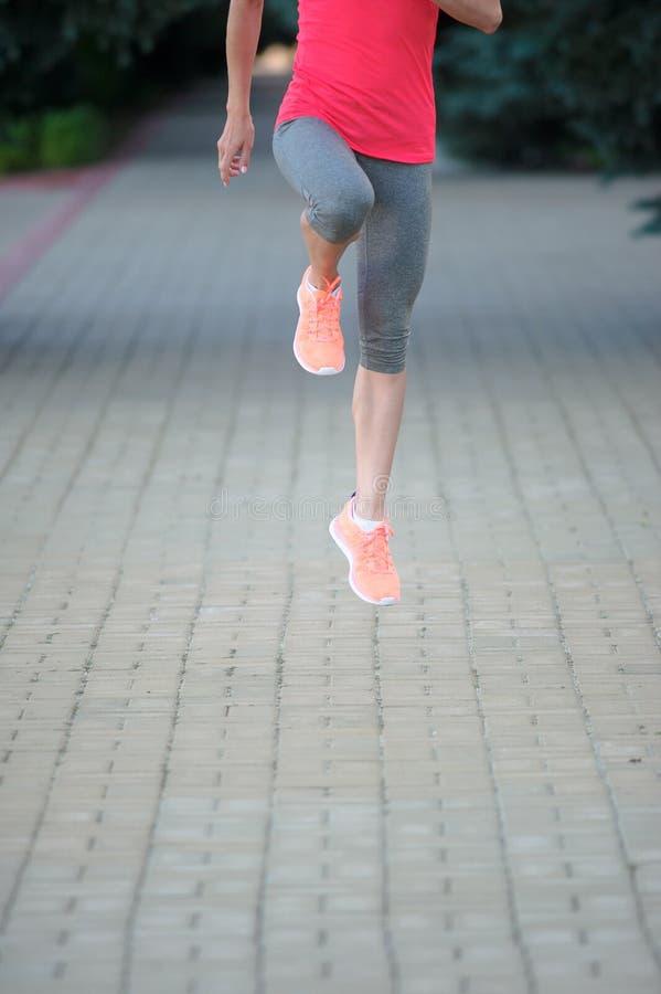 Idrotts- kvinna som sträcker hennes ben och förbereder sig för körd maraton arkivfoton