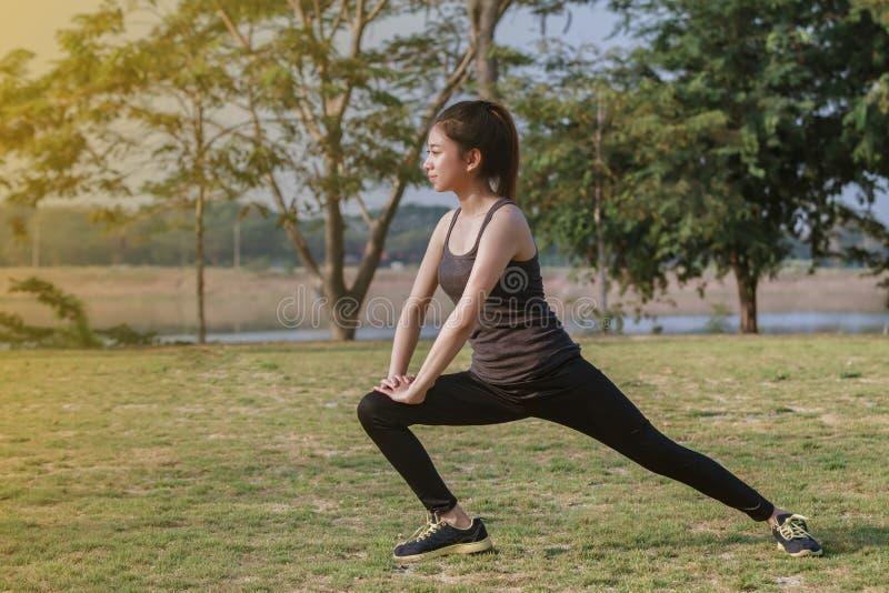 Idrotts- kvinnaasiatuppvärmning och ungt sammanträde för kvinnlig idrottsman nen arkivfoton