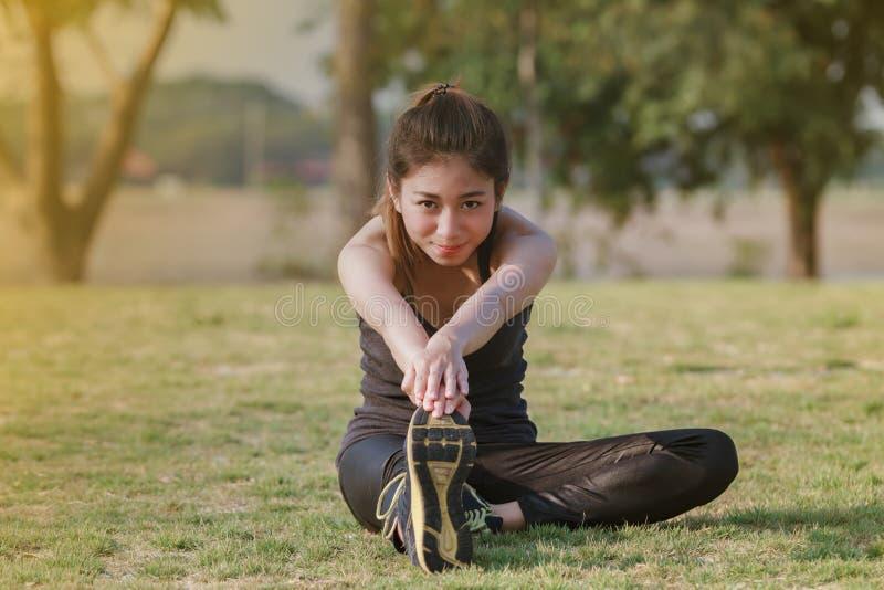Idrotts- kvinnaasiatuppvärmning och ungt sammanträde för kvinnlig idrottsman nen royaltyfri bild