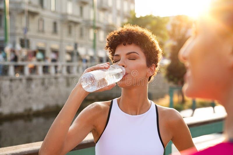 Idrotts- kvinnadricksvatten efter genomkörare royaltyfri fotografi
