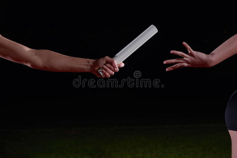 Idrotts- löpare som passerar taktpinnen i stafett royaltyfri foto