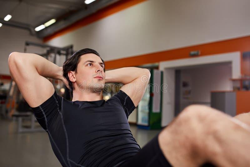 Idrotts- man i den svarta sportwearen som arbetar med hans buk- på simulatorn i idrottshall arkivfoton