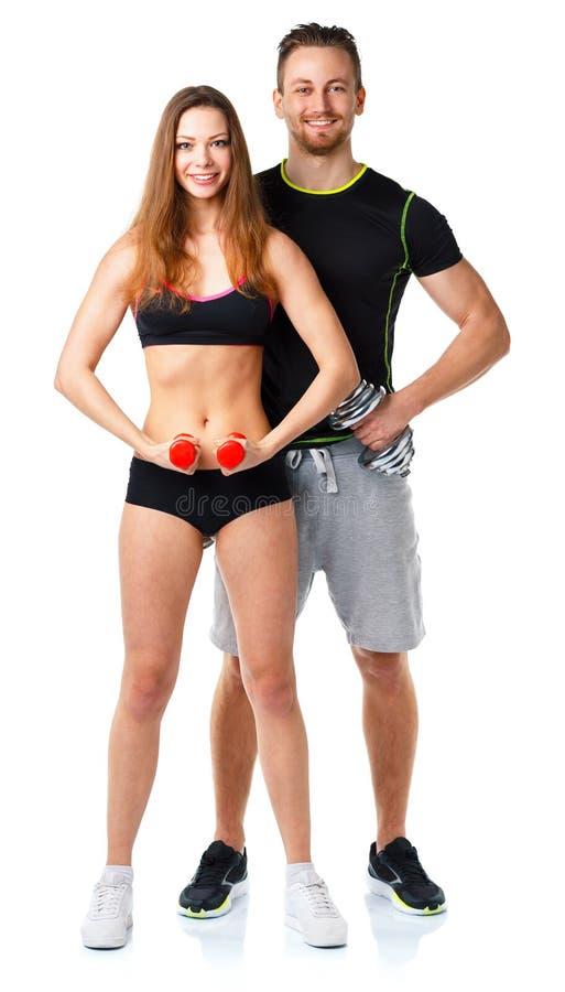Idrotts- man och kvinna med hantlar på viten arkivfoto