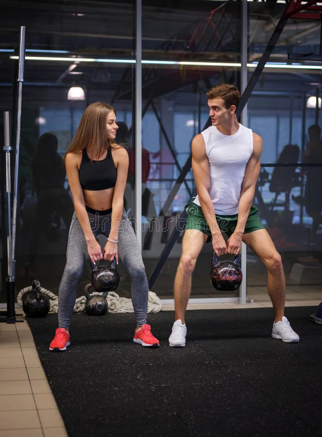 Idrotts- man och kvinna som utför en funktionell övning med kettlebells på en bakgrund för konditionklubba Sportbegrepp fotografering för bildbyråer