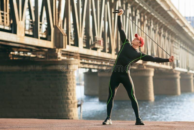 Idrotts- man som gör sträcka övningar som är utomhus- Aktiv manlig utarbetande yttersida på bakgrunden av bron royaltyfri foto