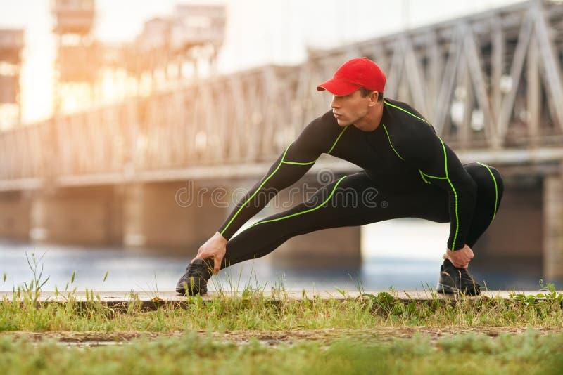 Idrotts- man som gör sträcka övningar som är utomhus- Aktiv manlig utarbetande yttersida på bakgrunden av bron arkivfoto
