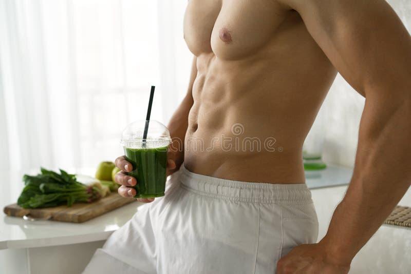 Idrotts- man som rymmer en grön smoothie arkivbild