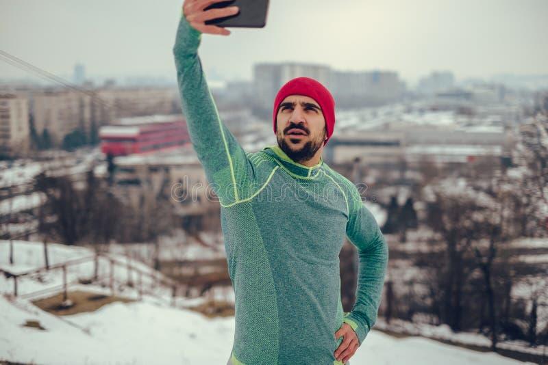 Idrotts- man som tar selfiefotoet över staden med telefonen royaltyfria bilder
