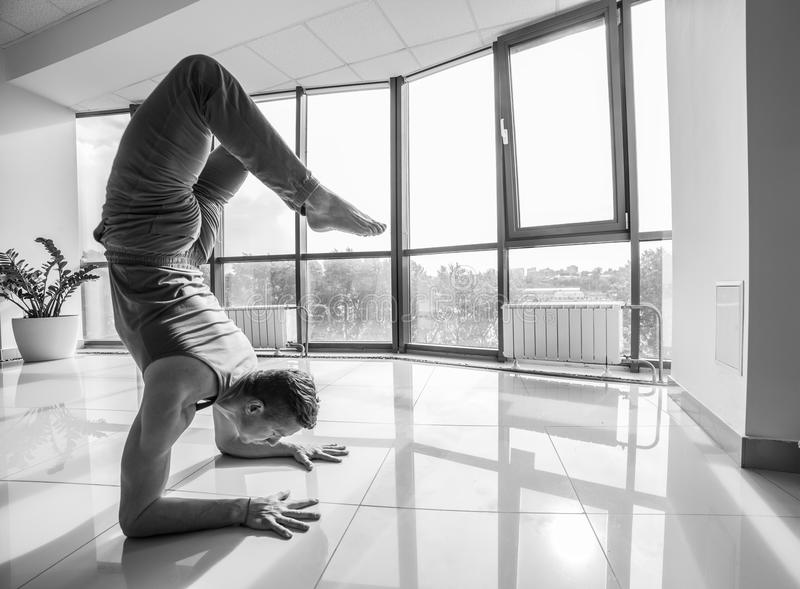 Idrotts- muskulös ung man som utarbetar, yoga arkivbilder