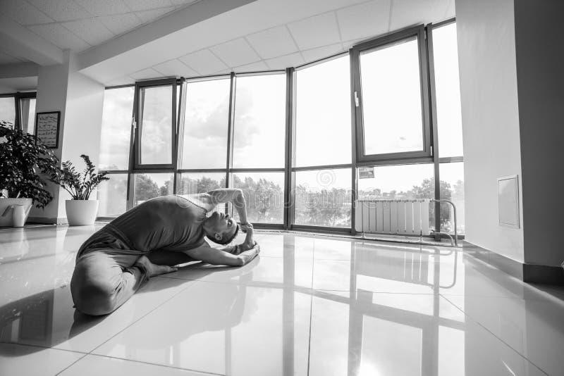 Idrotts- muskulös ung man som utarbetar, yoga royaltyfria foton