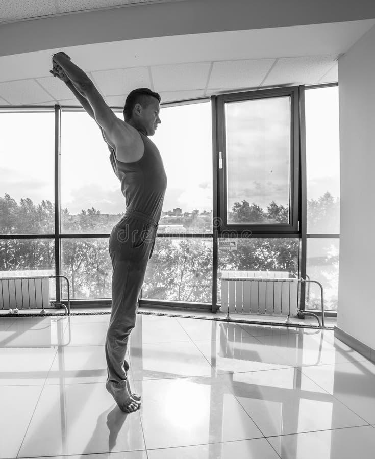 Idrotts- muskulös ung man som utarbetar, yoga arkivbild