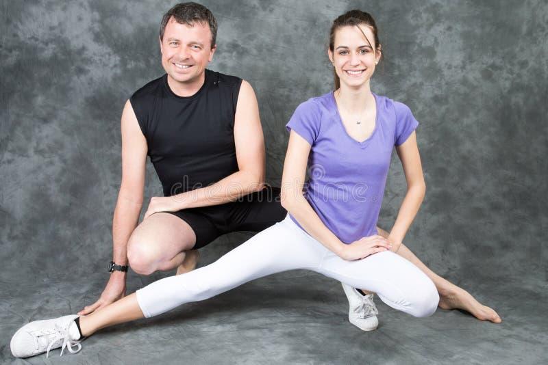 Idrotts- par man den personliga instruktören och kvinnan efter lagledareövningskondition, sporten som utbildar royaltyfri foto