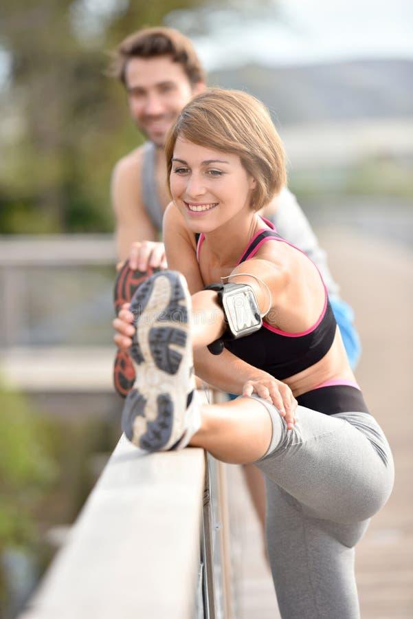 Idrotts- par som sträcker ben, når att ha joggat royaltyfri bild