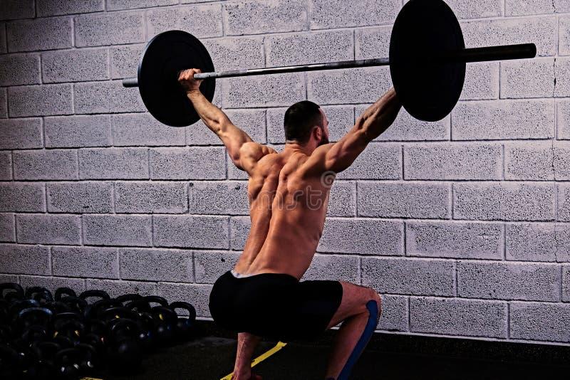 Idrotts- shirtless man som gör squats med en skivstång under hans honom fotografering för bildbyråer