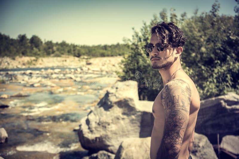Idrotts- shirtless ung man som är utomhus- på flod- eller vattenströmmen arkivbilder