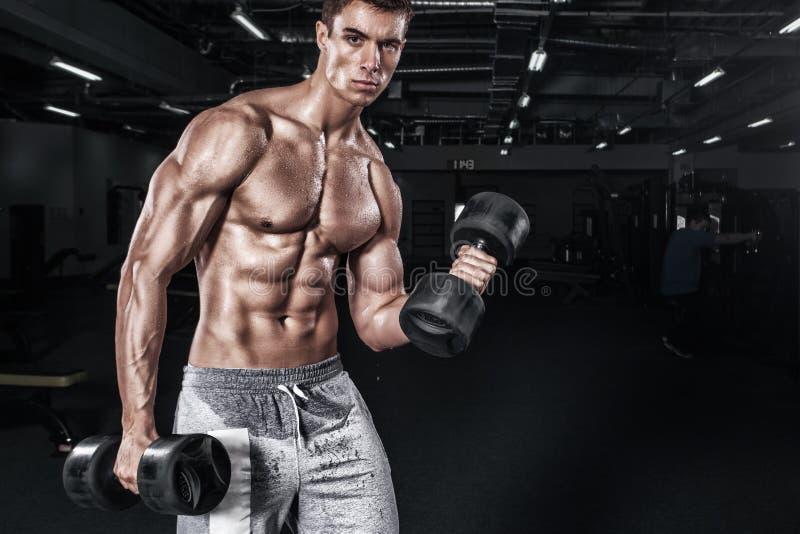Idrotts- shirtless ung sportman - konditionmodellen rymmer hanteln i idrottshall Kopieringsutrymmeför din text arkivbilder