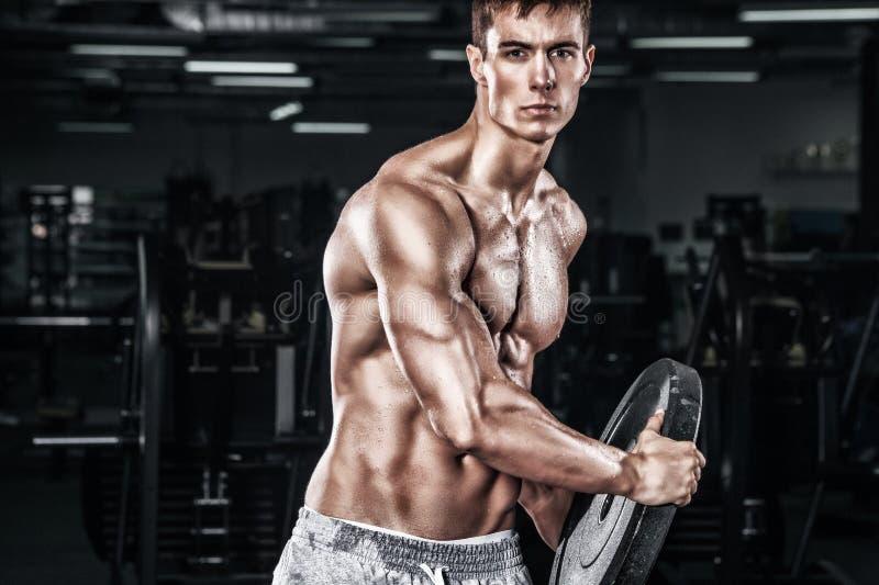 Idrotts- shirtless ung sportman - konditionmodellen rymmer hanteln i idrottshall Kopieringsutrymmeför din text royaltyfria foton