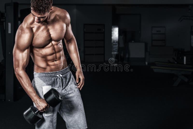 Idrotts- shirtless ung sportman - konditionmodellen rymmer hanteln i idrottshall Kopieringsutrymmeför din text arkivbild