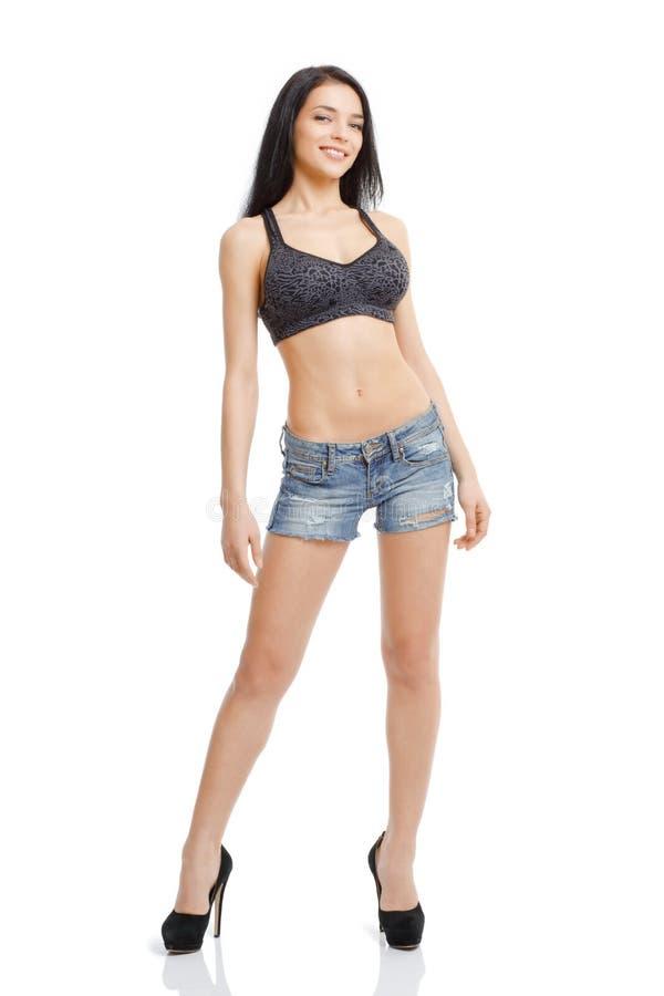 Idrotts- slank flicka i grov bomullstvillkortslutningar och en isolerad sportklänningsliv arkivfoto