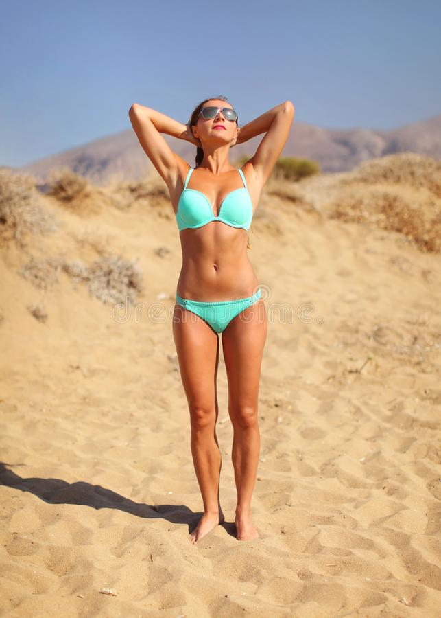 Idrotts- slank ung kvinna i den cyan bikinin som rymmer henne handbehi arkivfoton