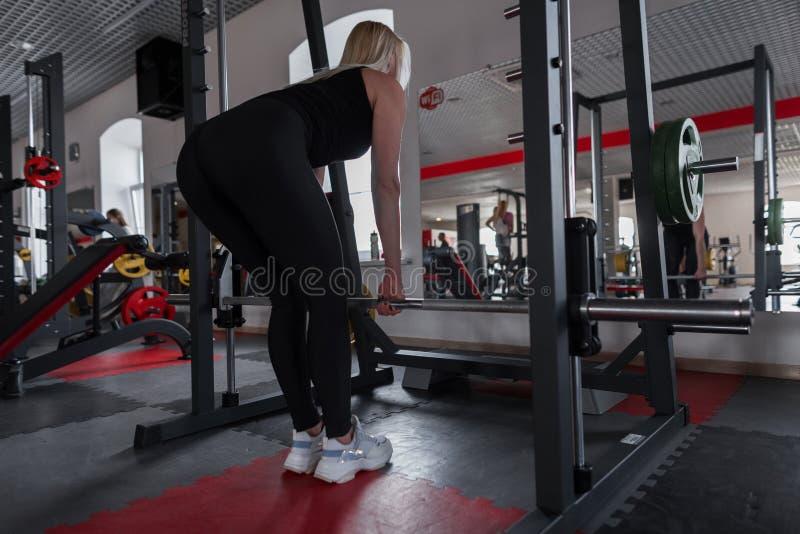 Idrotts- ung härlig kvinna i den svarta sportswearen som gör övningar med en metallisk gam i en modern idrottshall Flickainstrukt royaltyfria bilder
