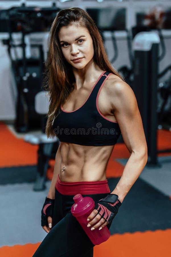 Idrotts- ung kvinna efter hård genomkörare på idrottshallen Konditionflickan rymmer shaker med sportive näring royaltyfria bilder