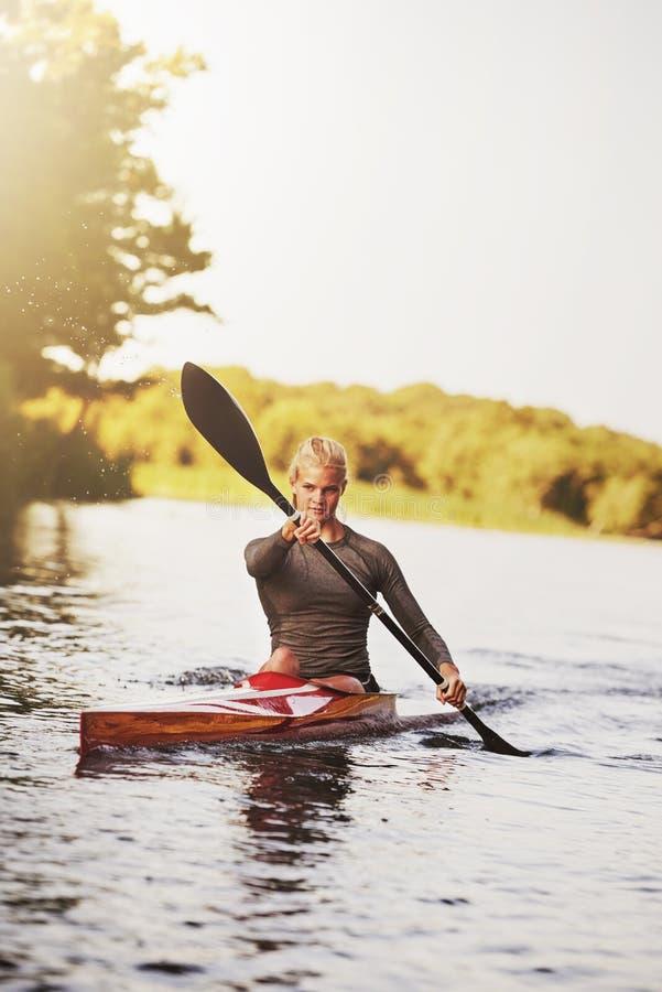 Idrotts- ung kvinna som paddlar på sjön i sommar royaltyfria bilder