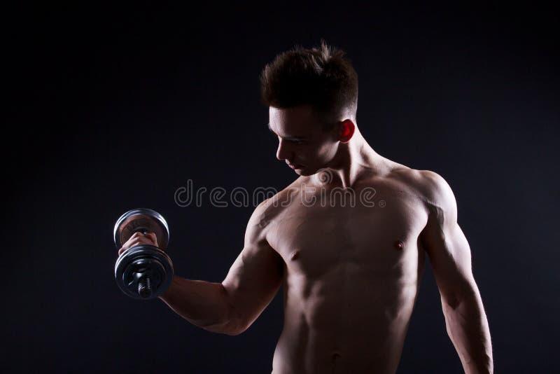 Idrotts- ung man med en hantel på en svart bakgrund Naken torso, muskulös kropp Starka bröstkorg- och skuldramuskler Sh studio arkivfoton