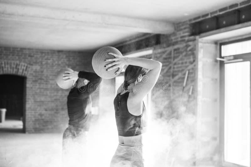 Idrotts- ung man och kvinna i sportswear som övar med medicinbollar i idrottshall arkivbild
