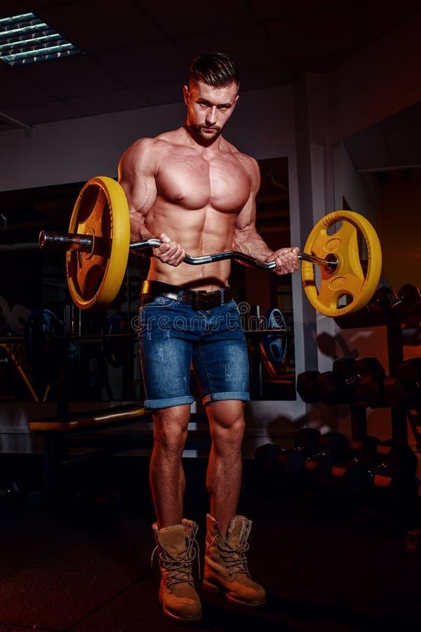 Idrotts- ung man som gör övningar med skivstången i idrottshall Den stiliga muskulösa kroppsbyggaregrabben utarbetar royaltyfria bilder