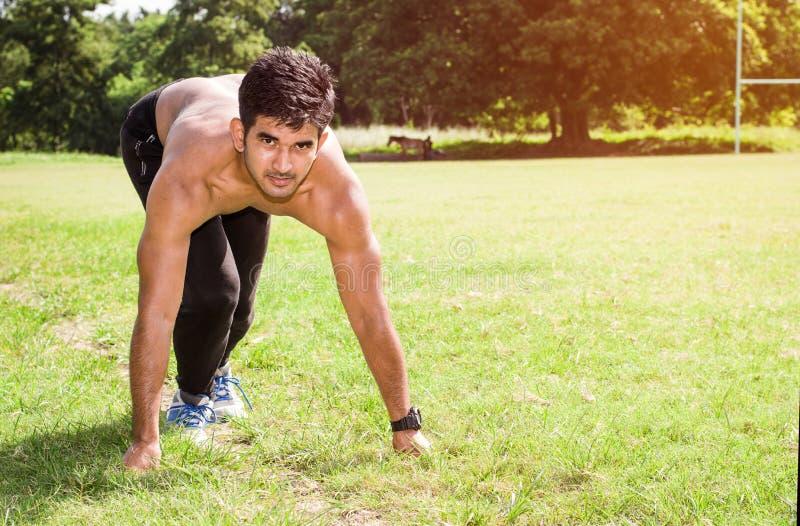 Idrotts- ung man som kör i sportjordningen Sunt livsstil-, kondition- och sportbegrepp royaltyfri fotografi