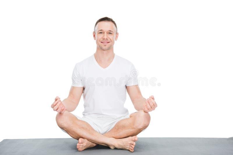 Idrotts- ung man som sitter på matt yoga och att meditera royaltyfri foto