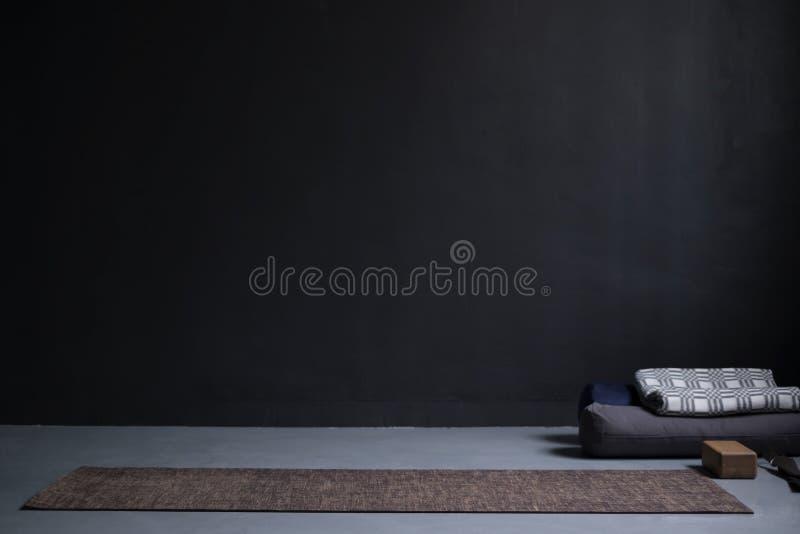 Idrottshallinre med matt yoga och stöttor Inga personer Kopieringsutrymme på den svarta väggen royaltyfri fotografi