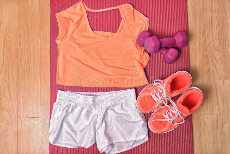 Idrottshallkonditionkläder på golvet för hemmastadd bästa sikt för styrkautbildningsgenomkörare Orange matcha t-skjorta och sprin royaltyfria bilder