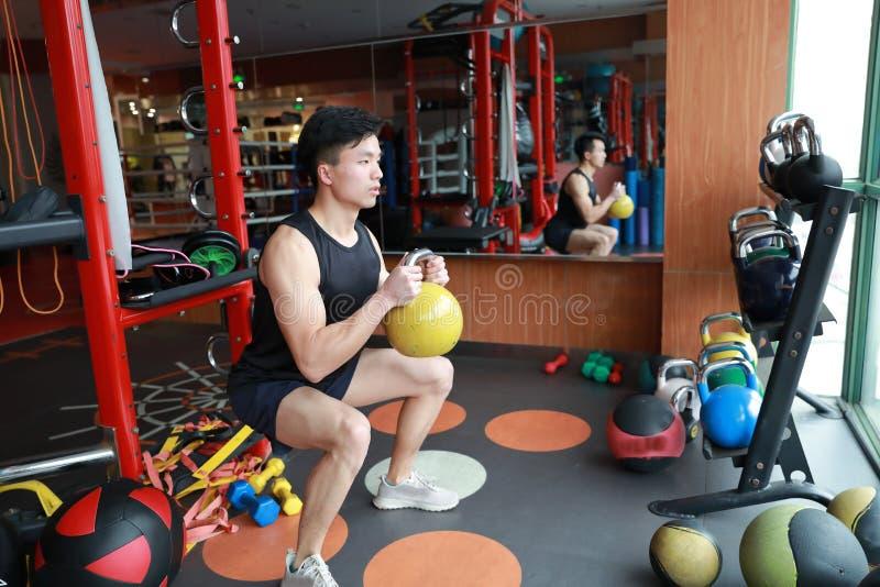 Idrottshallman i idrottshall som utarbetar genom att använda kettlebells inomhus Härligt press royaltyfri fotografi